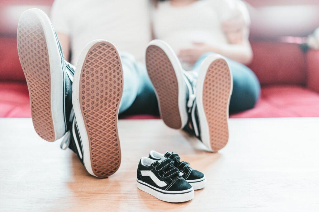 2 paires de pieds de parents avec des chaussures de bébé pour illustrer notre nouvelle vie à 3